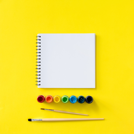 note book row rainbow paints and brushes flat lay top view copy space yellow background minimalist composition school stationery Stock Photo