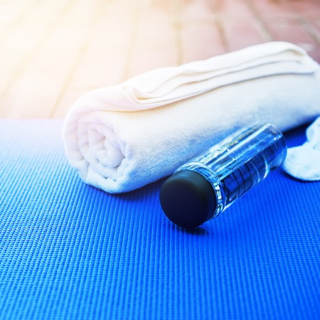 set for exercises yoga bottle water blue rug white towel against nature background open air morning time equipment Stock Photo
