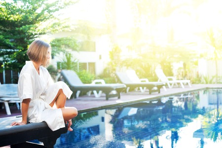 young woman white dressing gown sitting near swimming pool resort area concept recovery health vacation morning time open air view copy space