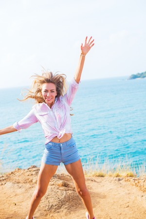 portrait smiling happy blonde long fare hair girl having fun jump up shore island sea morning landscape open air view sunny day