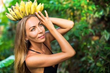 banana goddess young beautiful woman in tropical jungle caucasian suntan girl with bunch fruits as crown concept nature abundance 스톡 콘텐츠