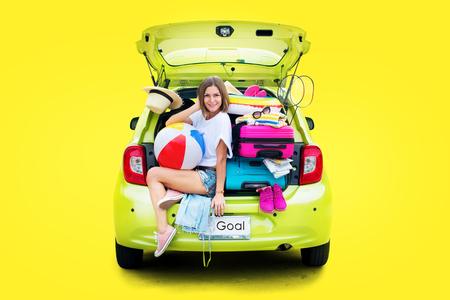 Bereit zu reisen. Frau im grünen überladenen Auto mit Sachen Sachen vor Reise. Helle Koffer Gepäck Full Stuff Zubehör Kleidung Ballon. Sommerkonzept-Feiertagsabenteuer lokalisiert auf Gelb