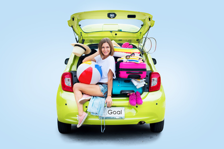 Ready to travel. Woman before Trip in Green Overloaded Car with Things. Bright Suitcases Luggage Accessories Clothes. Summer Concept Holiday Adventure Isolated on Blue