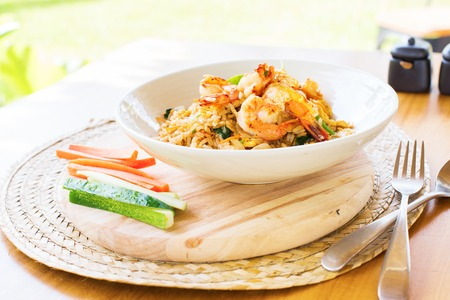 Khao pad with shrimp with vegetables cucumber and carrot serve white plate Thai traditional cuisine Restaurant food