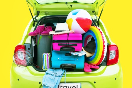 Overloaded Green Car Bright Suitcases Summer Accessories Things Slippers Hat Ballon Rackets. Concept Summer Holiday Travel Family Trip Background Isolated Yellow Imagens