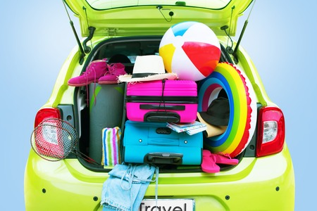 Overloaded Green Car Bright Suitcases Summer Accessories Things Slippers Hat Ballon Rackets. Concept Summer Holiday Travel Family Trip Background Isolated on Blue