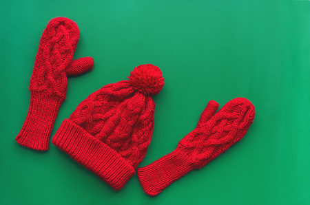 Christmas card two knitted hat and two mittens from red yarn on green backdrop.
