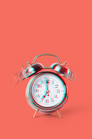 Ringing twin bell on retro classic alarm clock showing seven o'clock. Copy space on vertical image. Concept back to school. Glitch modern effect. Coral color background
