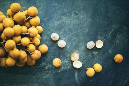 Longan fruit referred to as dragon eye fruit in branch on dark background. Super food tropical local product of Thailand and China. Top view flat lay 写真素材