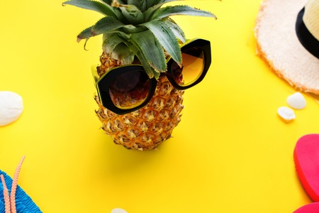 Stylized hero fruit major pine apple in glasses on a vacation. Yellow background. Creative concept of travel holidays Foto de archivo