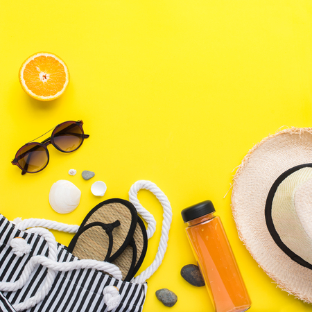Set of beach things accessories hot season. Straw hat, natural flip flops, shells, glasses, fruits on yellow background. Flat lay. Color concept of travel or vacation holidays. Copy space 免版税图像