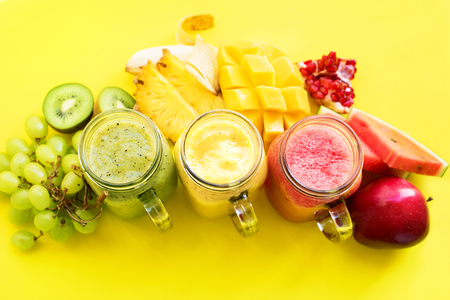 Fresh juices smoothie red green yellow Tropical fruits water melon apple kiwi mango banana pine apple pomegranate grape on yellow background. Selective focus bottles multi-colour. Top view
