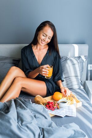 Breakfast in bed as surprise for Valentines Day to young beautiful brunette woman in black silk dressing gown. Gray colors in interior. Healthy food on tray fruit, orange juice, coffee, roll Stock Photo