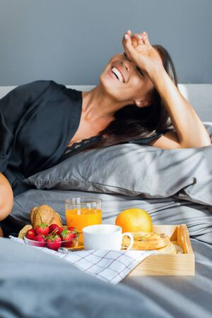 Breakfast in bed. Young beautiful brunette woman in black silk dressing gown eats strawberry from tray. Gray colors interior. Healthy food on tray fruit, orange juice, coffee, roll Stock Photo