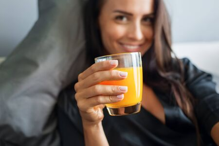 Breakfast in bed. Young beautiful brunette woman in black silk dressing gown drink orange juice. Gray colors interior.