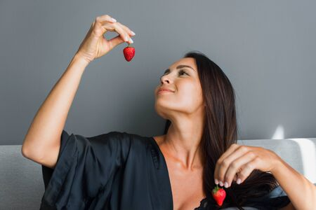 Breakfast in bed. Young beautiful brunette woman in black silk dressing gown eats strawberry. Gray colors interior Stock Photo