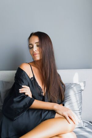 The young beautiful gentle suntanned brunette woman wakes up in bed. Gray colors in interior. Black silk dressing gown. Stock Photo