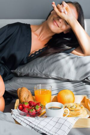 Breakfast in bed. Young beautiful brunette woman in black silk dressing gown eats strawberry from tray.