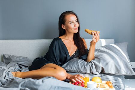 Breakfast in bed for holiday to young brunette beautiful smiling woman in black silk dressing gown. Gray colors in interior. Healthy food on tray fruit, orange juice, coffee, roll Stock Photo