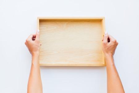 Mani femminili che tengono vassoio vuoto in legno. Donna in grembiule bianco nero grembiule. Vista dall'alto