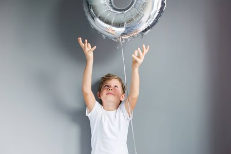 Happy boy with ballon number 8 on his birthday on gray wall. Happy childhood celebration concept.
