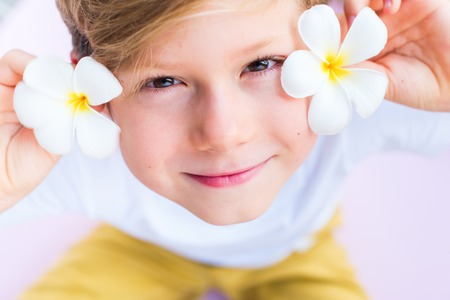Little cute caucasian boy holding frangipani or plumeria flower on pink background. Asian Songkran festival