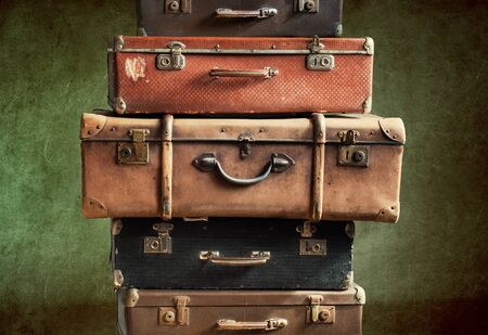 Antique retro pile of suitcases in stack. Vintage tower trunks on green shabby background. Travel concept luggage design