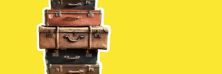 Vintage tower pile ancient suitcases. Travel concept luggage design. Long banner format yellow background