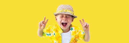 Enfant en chemise hawaïenne jaune et chapeau de paille crie fort du début des vacances, des vacances, du plaisir. Jaune isolé. Concept d'été
