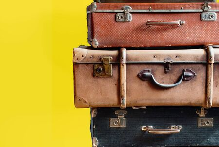 Vintage tower pile ancient suitcases. Travel concept luggage design. Isolated yellow ackground Stock Photo