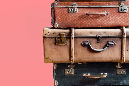 Vintage tower pile ancient suitcases. Travel concept luggage design. Isolated pink background