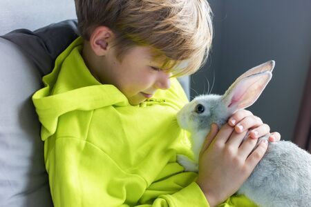 Happy little boy in yellow jacket playing with tame pet rabbit in the room
