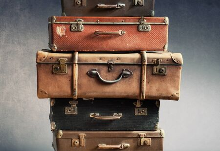 Antique retro pile of suitcases in stack. Vintage tower trunks on shabby background. Travel concept luggage design Stock Photo