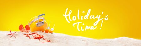 Holidays accessories suitcase, sea star, orange juice, bikini, slippers on sand beach. Sunny summer day. Travel and relax concept. Art collage yellow background hand written text