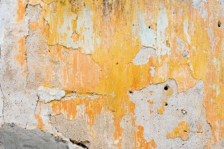 Old yellow concrete wall with cracked of stain of surface. Grunge vintage rustic
