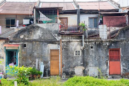 Ruined facades of houses from cement in Malaysia. Poor slums for accommodation of low segments of the population Stock Photo - 126471321