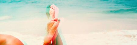 Suntaned womans foot with bracelet in focus relaxing lying on tropical beach in sunny day. Summer holiday traveling time. Glitch effect. Banner Stockfoto