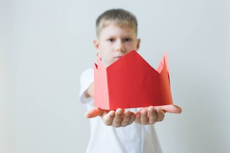 Boy gives red fake paper crown. Caricature concept of To give up positions in the government or make peace agreement. Copying of behavior model of the adult parent. Education problem 写真素材