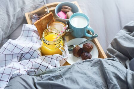 Morning breakfast in bed for couple. Orange juice, coffee, milk, muffins on wooden tray on grey linen sheet. Near pillow and coverlet in gray colors. Home interior. Copy space