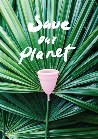 Text save our planet Women health concept, zero waste. Pink menstrual cup. Natural green palm leaves background. Alternative reusable product for female hygiene during periods. Minimalism