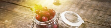 Ripe red cornel berries in small glass jar on old wooden country background. Autumn harvest wild usefull berries. Natural alternative treatment. Long banner 写真素材