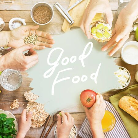 Good food concept text. Family table top view with hands holding and eating food. Healthy organic producys sandwiches and snacks. Template for own design