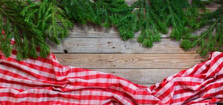 Holiday banner Christmas natural green fir tree spruce and checkered tablecloth on wooden planks vintage