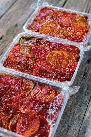 Tasty homemade dried tomatoes in containers on wooden background. Country style