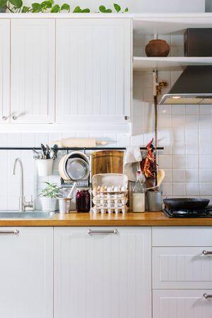 Dekorative Details der Küche getrockneter Pfeffer, Vintage-Löffel, Schneidebrett, Tablett, Teller auf Holztischplatte. Rustikale Landgerichte Geschirr, frische Lebensmittel verschiedene Sachen weißer Fliesenhintergrund