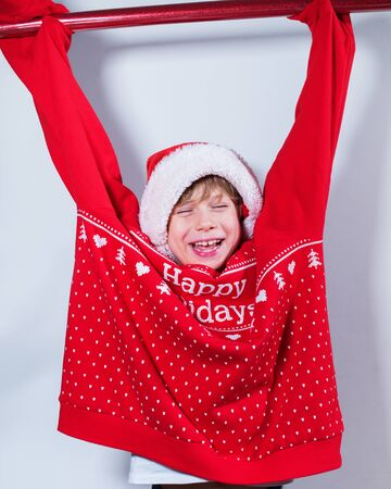 Charming boy wearing Santas Hat red sweater prepared to packing Christmas gifts and boxes into brightnes vintage wrapping paper Concept fun preparation to holidays Reklamní fotografie