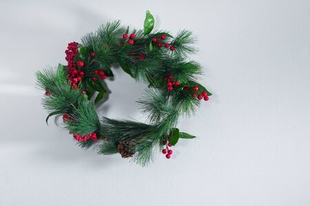 Holiday green Christmas decoration wreath on gray vintage wall. Happy New Year greeting card. Winter xmas theme