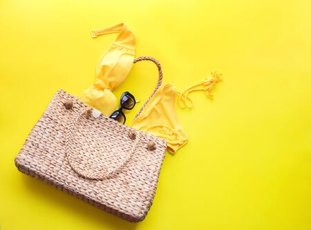Wattled bag and women's bathing suit on yellow background. Summer time top view flat lay. Copy space single object banner concept