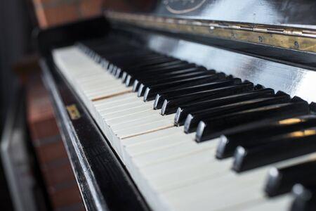 Old piano keyboard background with selective focus. Vintage retro instrument Foto de archivo