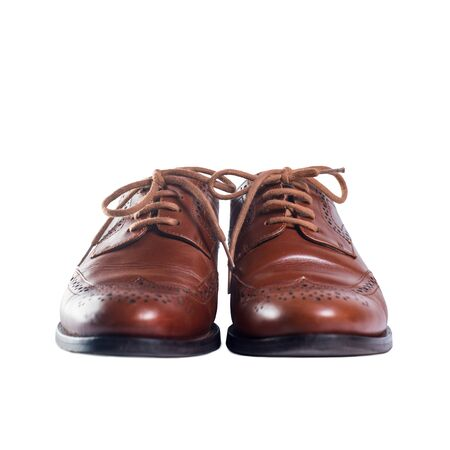 Classic brown leather pair of shoes standing front and isolated on white background. Objects and accessories. Stock Photo